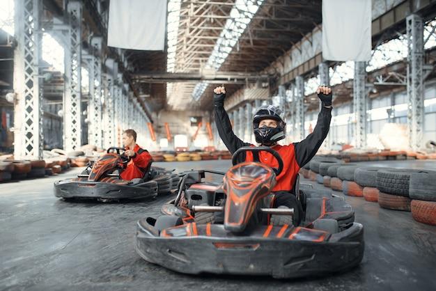 Go kart racer in helmet raised his hands up