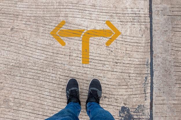 왼쪽이나 오른쪽으로 가십시오. 선택에 대한 생각, 전환점 개념에 서있는 사람