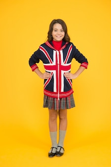 Go to london. learn english language. british school in england. vacation in great britain. travel concept. union jack flag. small girl uniform. kid with english flag on jacket. go study to england.