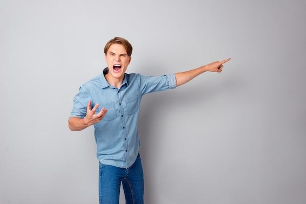 나가! 그의 직원 실수 자루에 대해 분노한 분노한 젊은 임원 관리자는 회색 벽 위에 고립 된 점 검지 손가락 copyspace 착용 청바지 셔츠를 기각