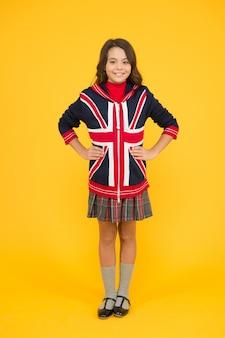 런던에 가다. 영어를 배우십시오. 영국의 영국 학교. 영국에서의 휴가. 여행 개념입니다. 유니온 잭 플래그. 작은 소녀 유니폼. 재킷에 영어 플래그와 함께 어린 아이입니다. 영국으로 유학을 가다.