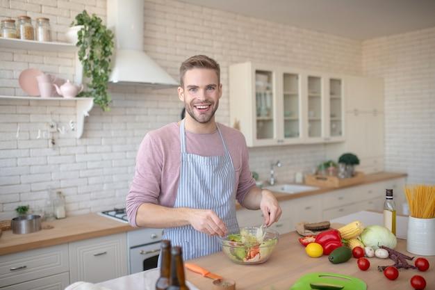 비건 채식을하세요. 맛있는 베레 테리아 요리를 준비하는 웃는 젊은 남자