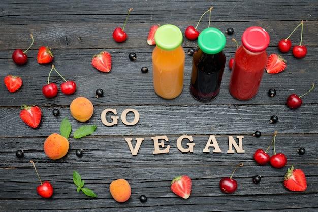 Три бутылки с соком, фруктами и надписью go vegan. черный деревянный фон. концепция питания