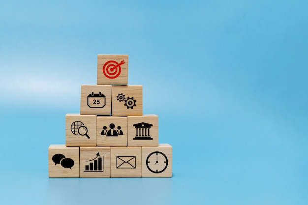 Goal. business finance icon on wooden cube block pyramid stack on blue background with copy space, online marketing, banking, investment, business strategy, internet technology and financial concept