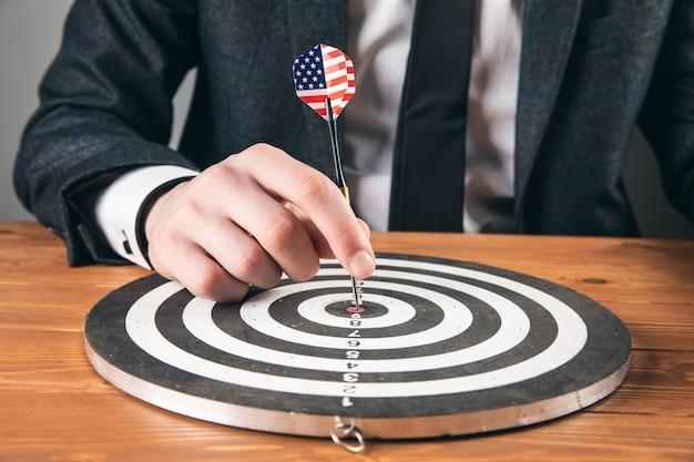 Концепция цели. мужчина кладет дротик в центр круга