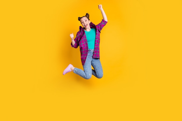 Goal. full size photo of attractive excited funky teenager lady jump up flight support sports team raise fists cheering wear casual plaid shirt shoes jeans isolated yellow color background