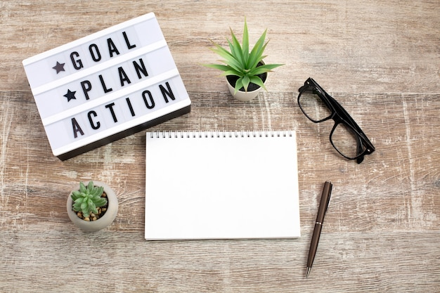 Goal, plan, action text on light box and notebook