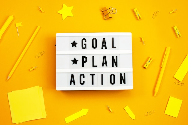 Goal, plan, action text on light box with office accessories on yellow.