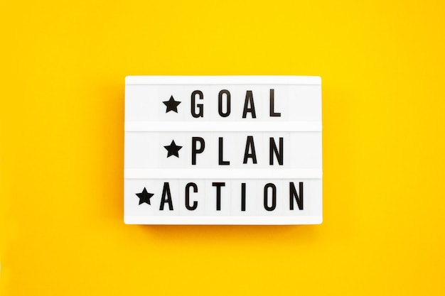 Goal, plan, action text on light box on yellow background.