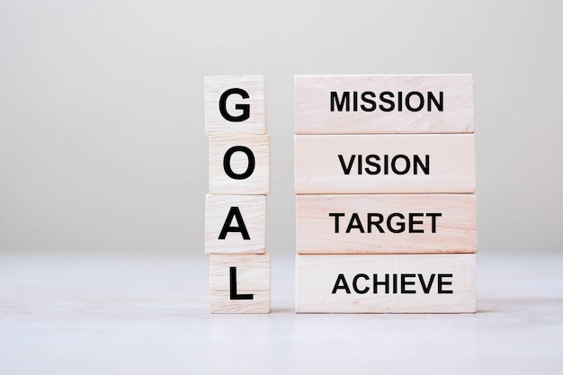 Goal text wooden cube with mission, vision, target and achieve blocks