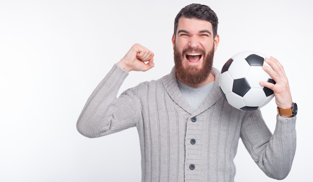 Цель! мы победили! молодой человек держит футбольный мяч, делая жест победителя.