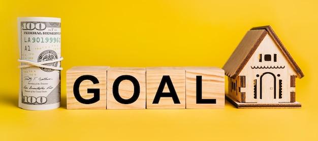 Цель с миниатюрной моделью дома и деньгами на желтом фоне.