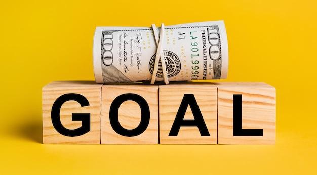 黄色い表面にお金でゴール。ビジネス、金融、クレジット、投資、税金の概念