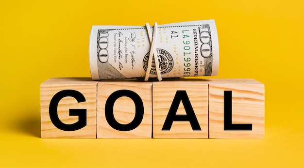 Goal with money on a yellow surface. the concept of business, finance, credit, investments, tax