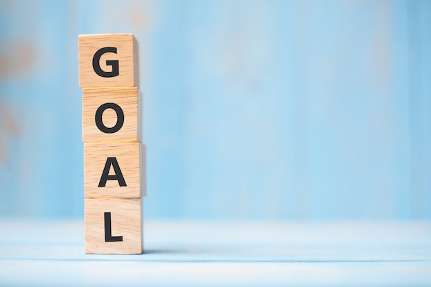 Goal wooden cubes on blue table background