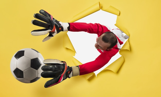 Goalkeeper exits from a hole and tries to tatches the ball. yellow background