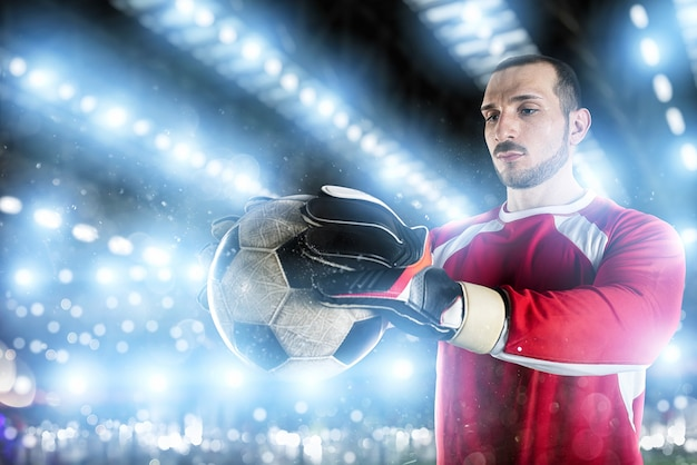 Goalkeeper holds the ball in the stadium during a football game
