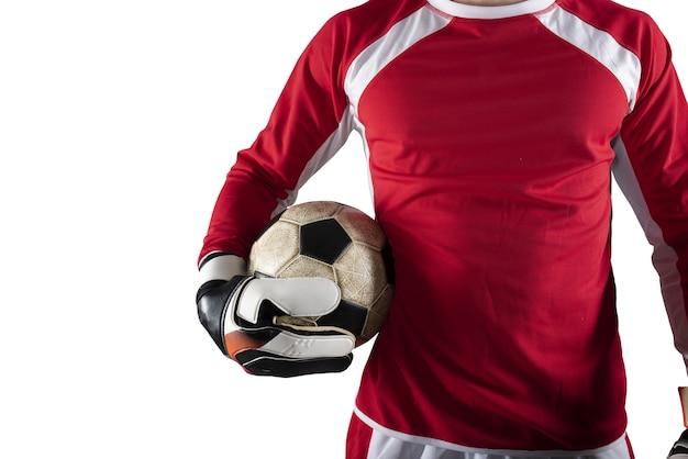 ゴールキーパーは、白い背景で隔離のフットボールの試合中にスタジアムでボールを保持します。