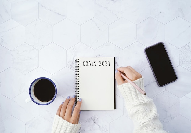 Goals 2021 on flat lay of woman writing on notebook and drinking hot cup of coffee and using smartphone on white marble background with copy space, new year resolutions concept