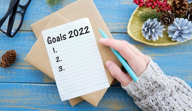 ペンとペーパークリップで青い背景のノートに書かれた目標2022。