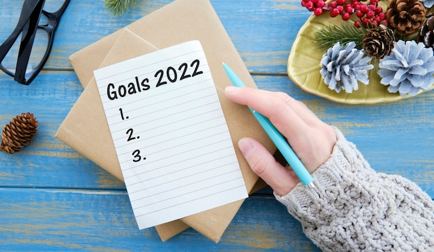 Goals 2022 written in a notebook on blue background with pen and paper clip.