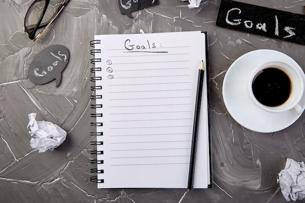 Goals as memo on notebook with idea, crumpled paper, cup of coffee