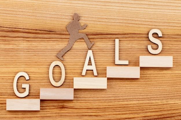 Концепция целей с лестницей успеха на деревянном столе.