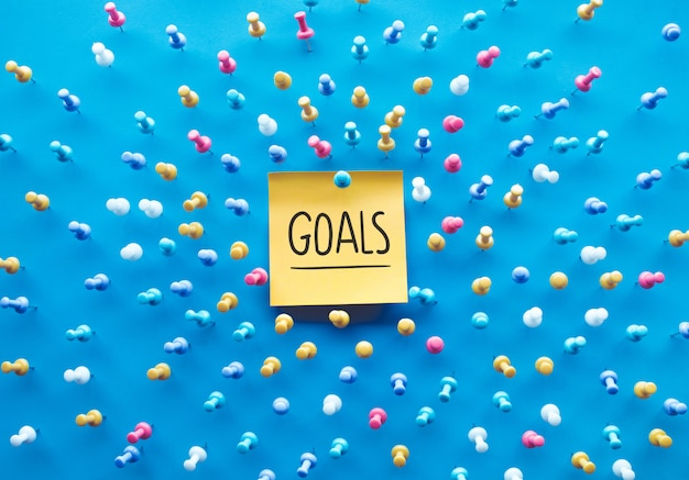 Goals concepts with text on notepaper and group of pin, thumbtack on blue