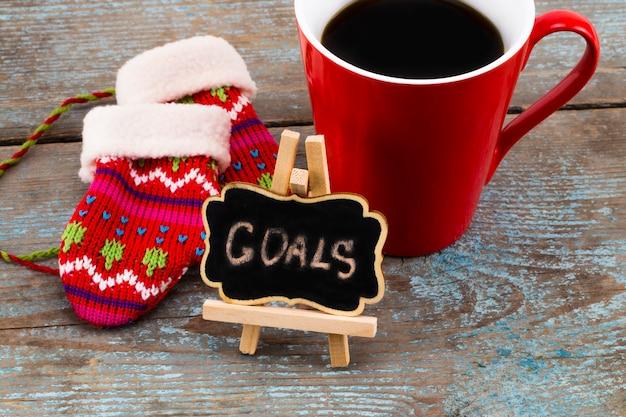 Цели - почерк сообщения на доске с чашкой кофе и варежками, концепция новогодних резолюций.