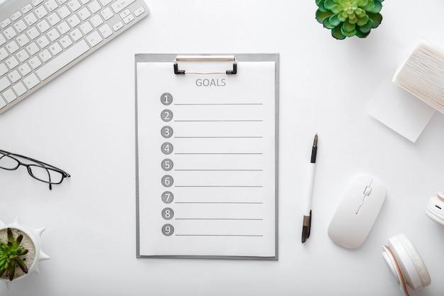 白い背景の上のワークスペースの目標リスト。フラットレイ、トップビューオフィステーブルデスク。キーボードマウスメガネペーパープラントラップトップを使用した自宅の作業スペースに関する新しいアイデア。
