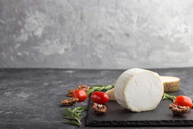 ヤギのチーズとさまざまな種類のチーズと黒いコンクリート背景に黒いスレート板にトマト