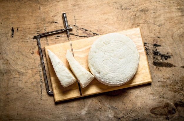 Goat cheese on cutting board on wooden table.