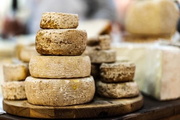 木の板に積み上げられた山羊のチーズの頭