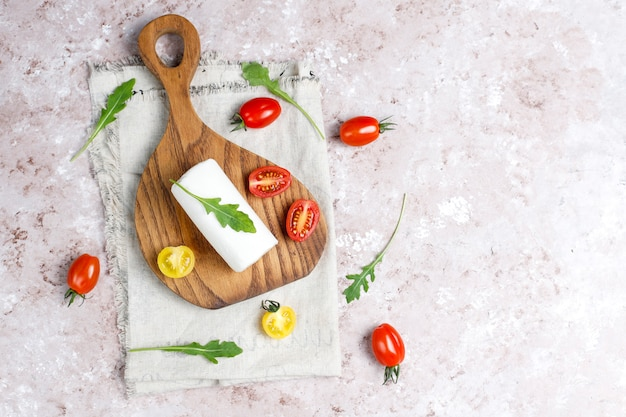 Goat cheese slices on wooden board with ruccola,cherry tomatoes. ready to eat.