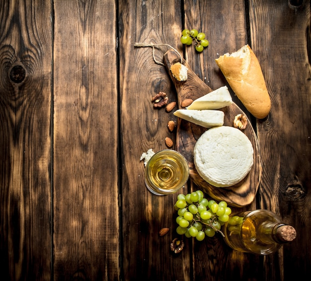 화이트 와인과 견과류를 곁들인 염소 치즈. 나무 테이블에.