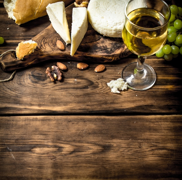 木製のテーブルに白ワインとナッツと山羊のチーズ。