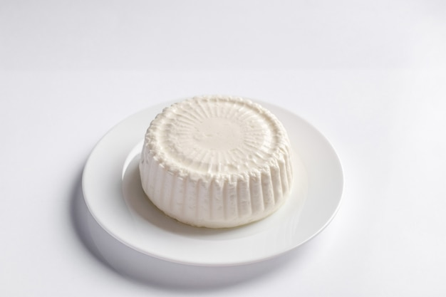 Goat farm cheese feta on white round plate