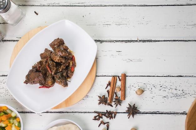Козий сатай на белой тарелке и на деревянной разделочной доске традиционные индонезийские блюда