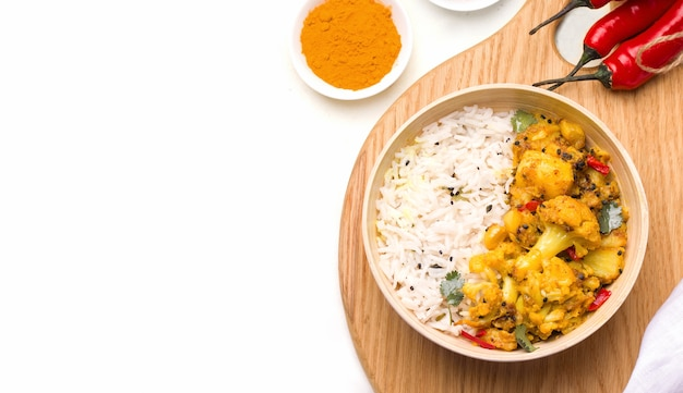 Gobi aloo indian vegetarian dish of vegetables and potatoes in a bowl on a wooden board on white