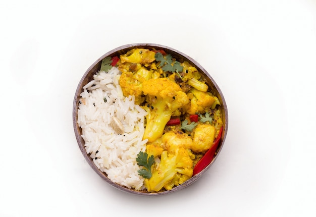 Gobi aloo traditional indian vegetarian dish of cauliflower in a plate with rice on white