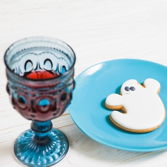 Goblet and ghost cookie on wooden table