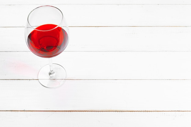 Бокал красного вина на деревянный стол на фоне деревянных стен