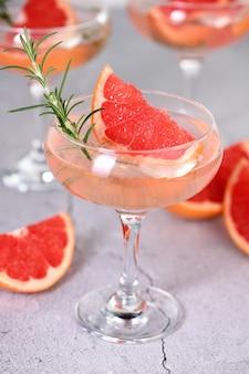 グレープフルーツのスライスとローズマリーの小枝とスパークリングワインのゴブレット