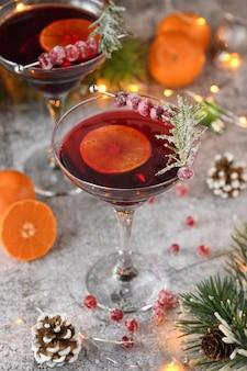 Бокал с клюквой маргарита с засахаренной клюквой, розмарином и мандарином рождественская вечеринка