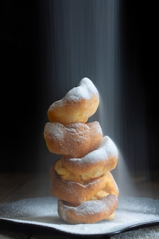 Goblet of yorkshire puddings with pouring powdered sugar