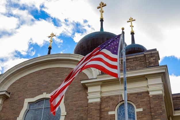 神はアメリカを祝福しますアメリカの国旗と古い教会の尖塔は教会と国家の分離を反映しています