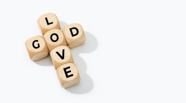 神は愛の概念です。白い背景で隔離のテキストとクロスを形成する木製のブロック。コピースペース