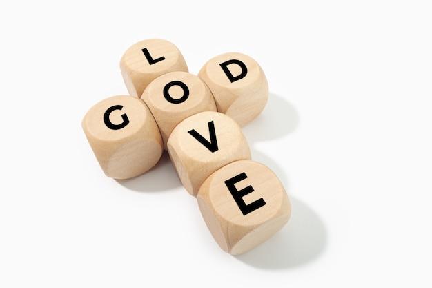 神は愛の概念です。白い表面に分離されたテキストとクロスを形成する木製のブロック