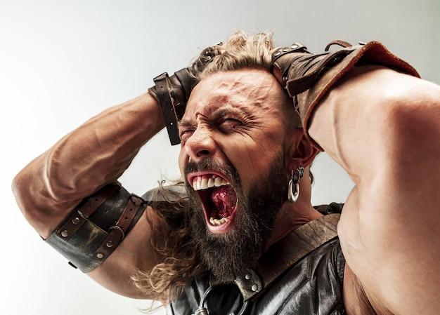 Бог грома. светлые длинные волосы и мускулистая мужская модель в кожаном костюме викинга с косплеем большого молотка на белом фоне студии. фэнтезийный воин, античная концепция битвы.