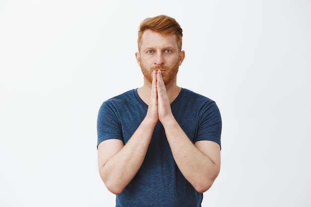 God please hear my prayers. determined and focused attractive male redhead entrepreneur being worried for business, holding hands in pray over lips and staring patiently, waiting for miracle